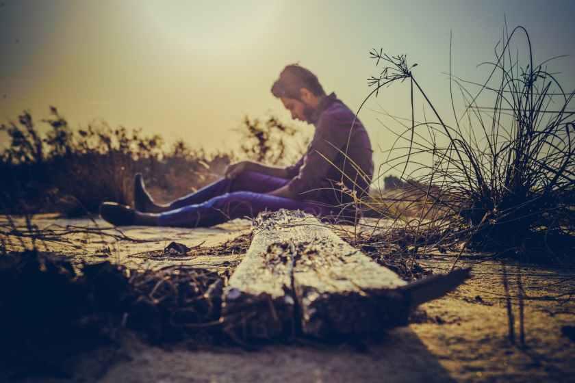 man sitting near brown wood plank